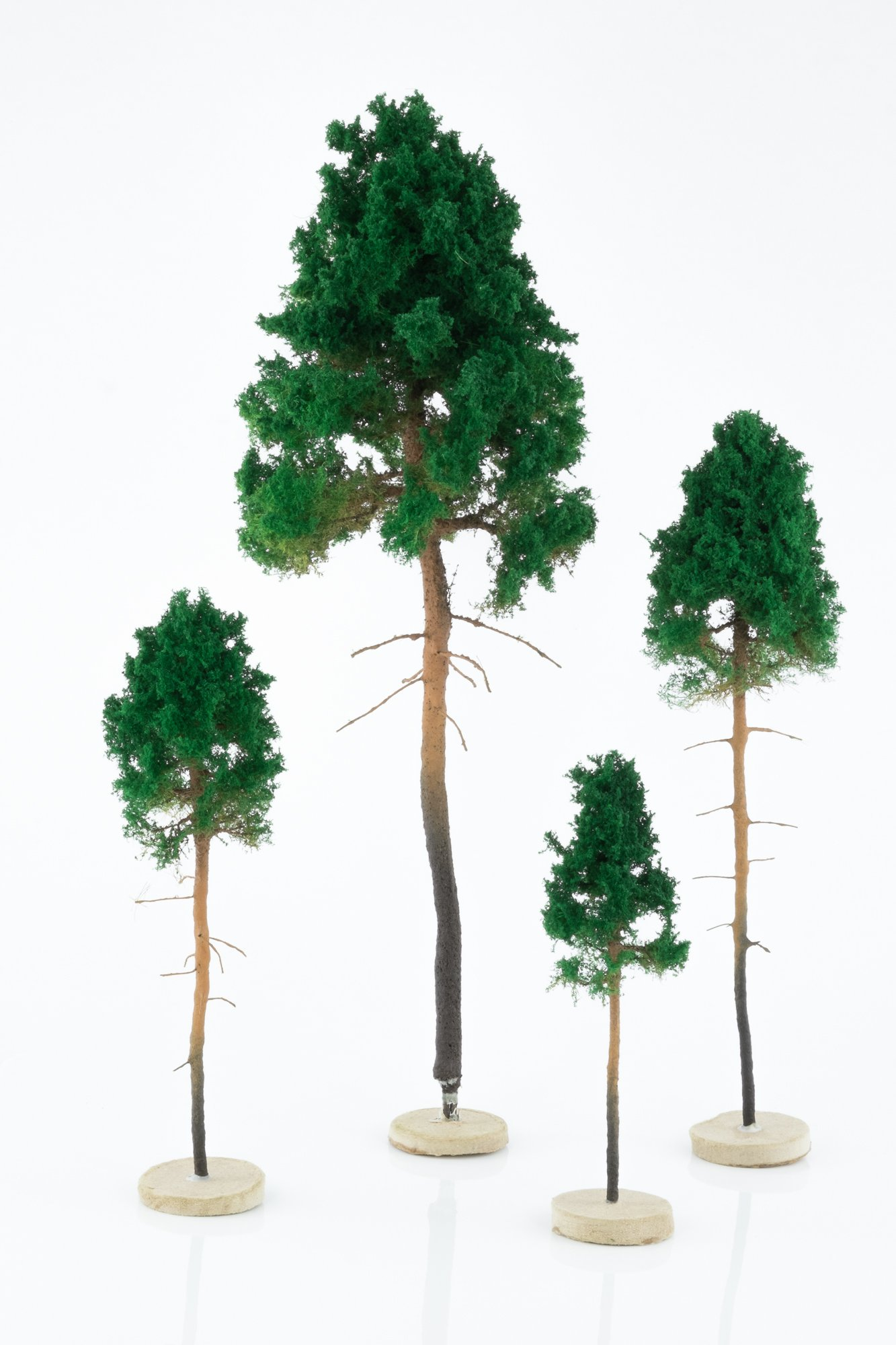 Four, green, young pine model trees. Size from 8 to 28 cm. Made from high quality model supplies by Primo Models.